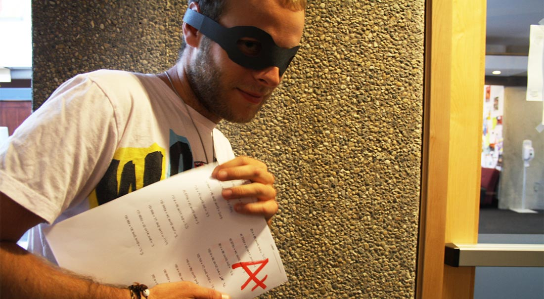 a photo of a guy with a mask holding an A+ paper