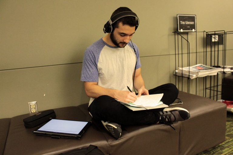 Student taking notes and listening to music with his Ipad next to him