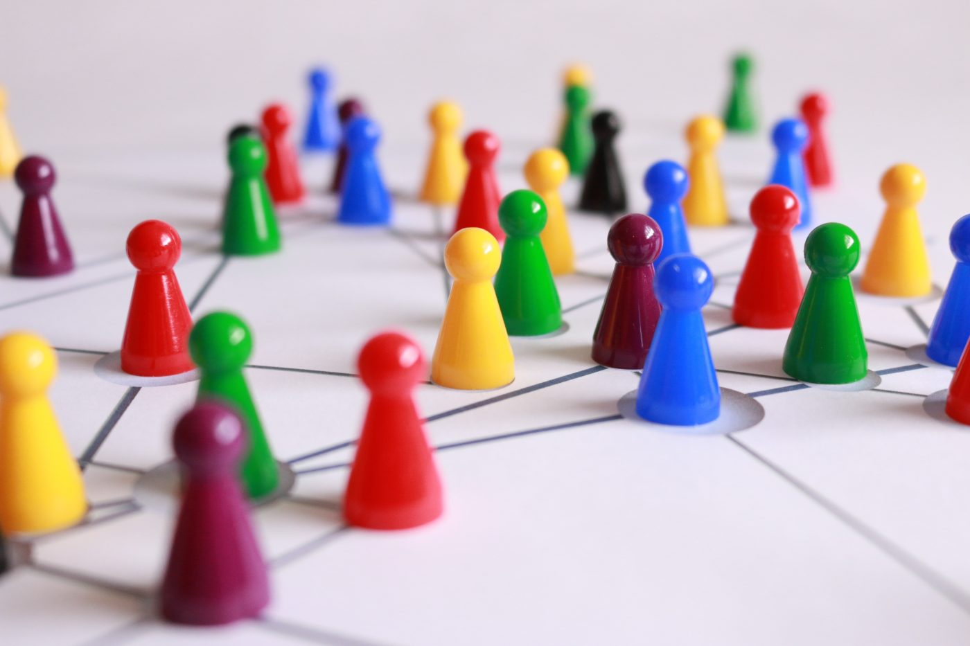 Several different colors of board game pieces connected by lines on paper