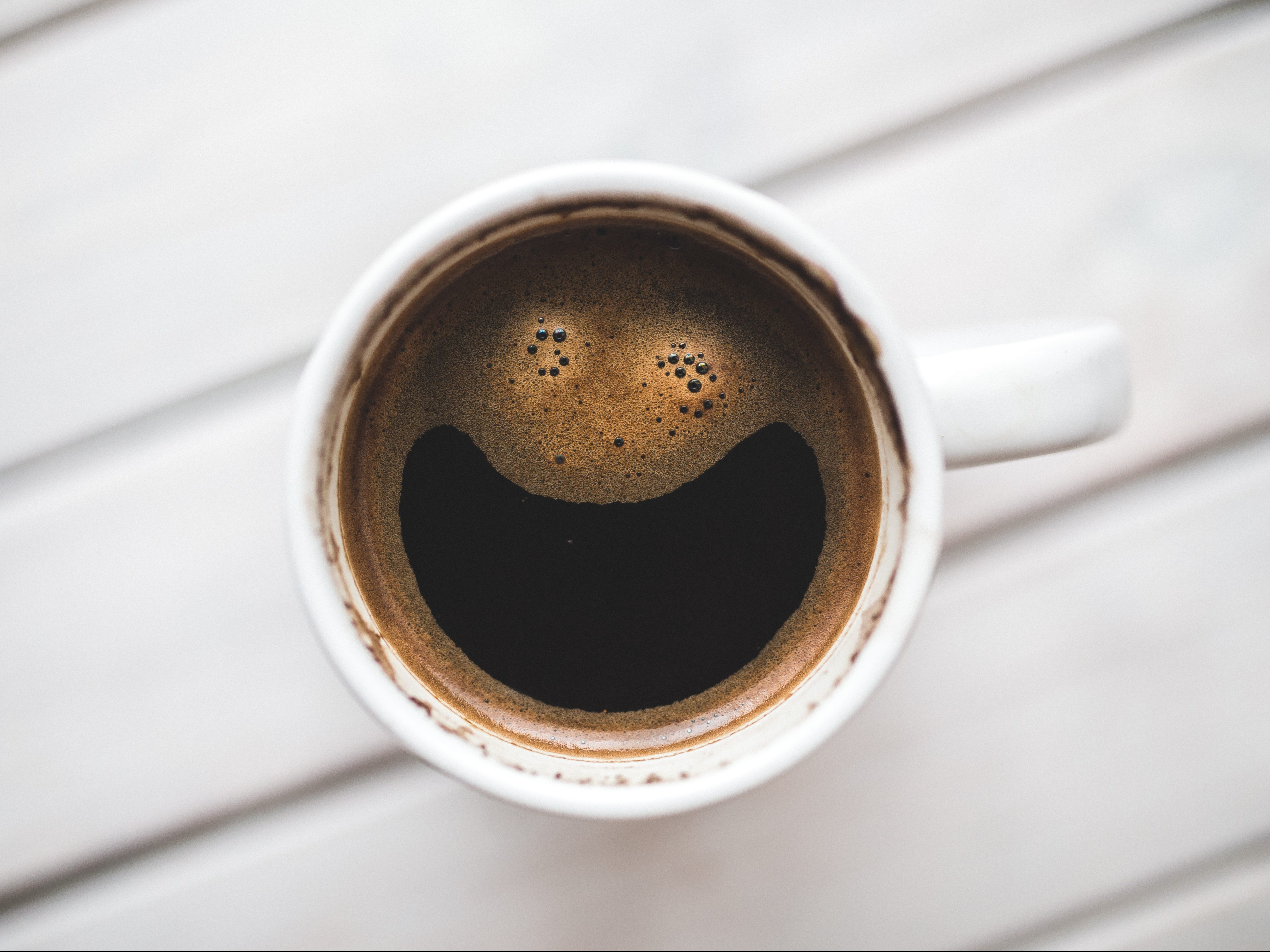 coffee in a mug in the shape of a smiley face
