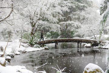 Snow falling on a bridge over a small lake