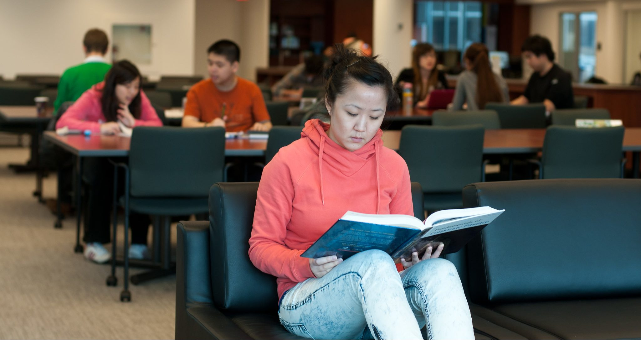Student studying in a chair with a book open